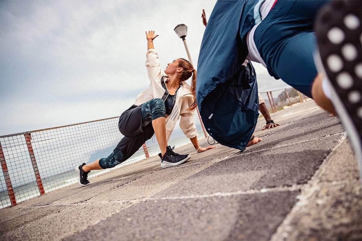 Dos personas entrenando y haciendo estiramientos al aire libre