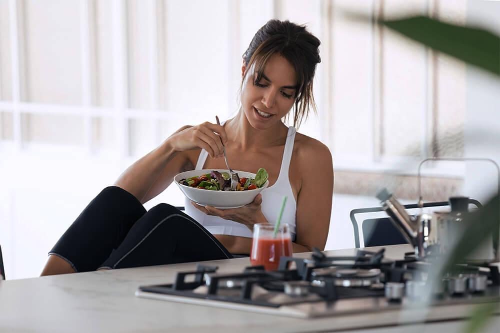 Donna che mangia insalata in cucina