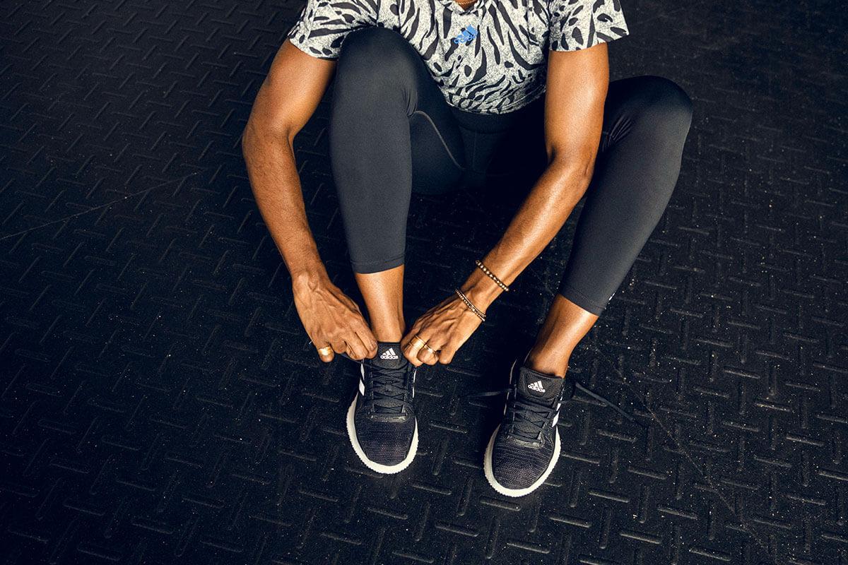 Mulher calçando os tênis para treinar em vez de cair na tentação de mais um lanche