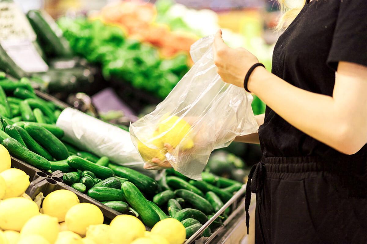 Une femme utilise un sac plastique pour y mettre des citrons