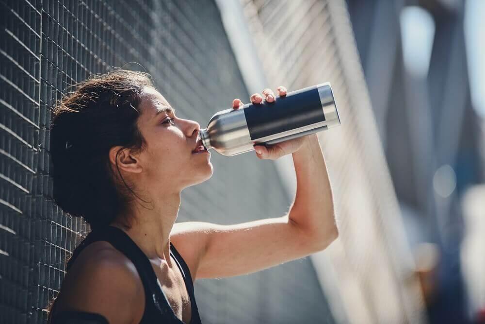 Une jeune femme boit après son entraînement