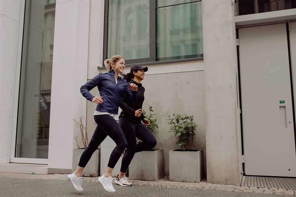 Zwei junge Frauen laufen durch eine Stadt