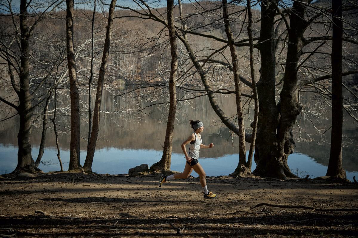 Une femme qui fait un trail dans la forêt