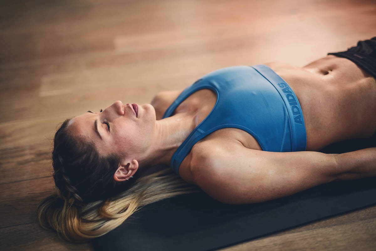 A young woman is laying on the yoga mat with her eyes closed