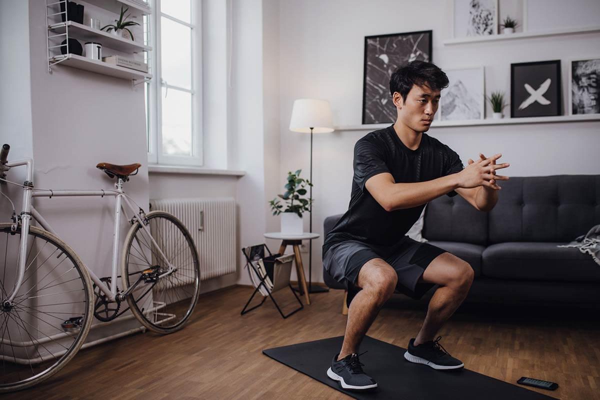 Uomo fa squat a casa