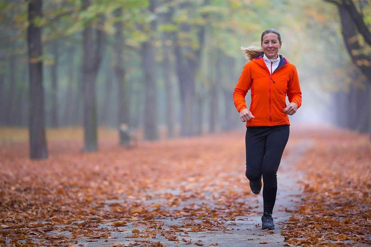 Une femme court dans la forêt en automne