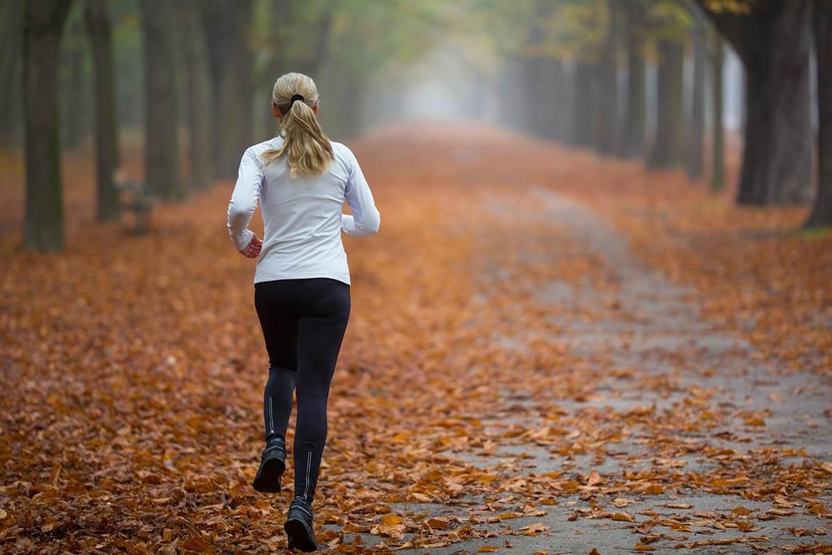 une femme court dans un parc en automne