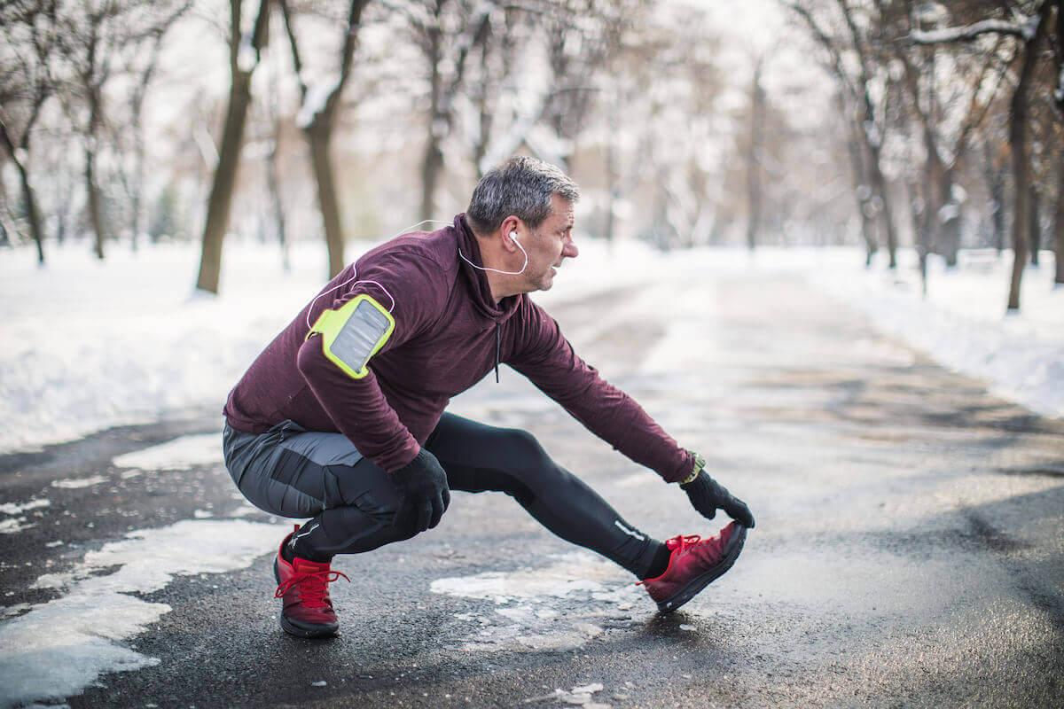 un homme court en hiver dans un bois