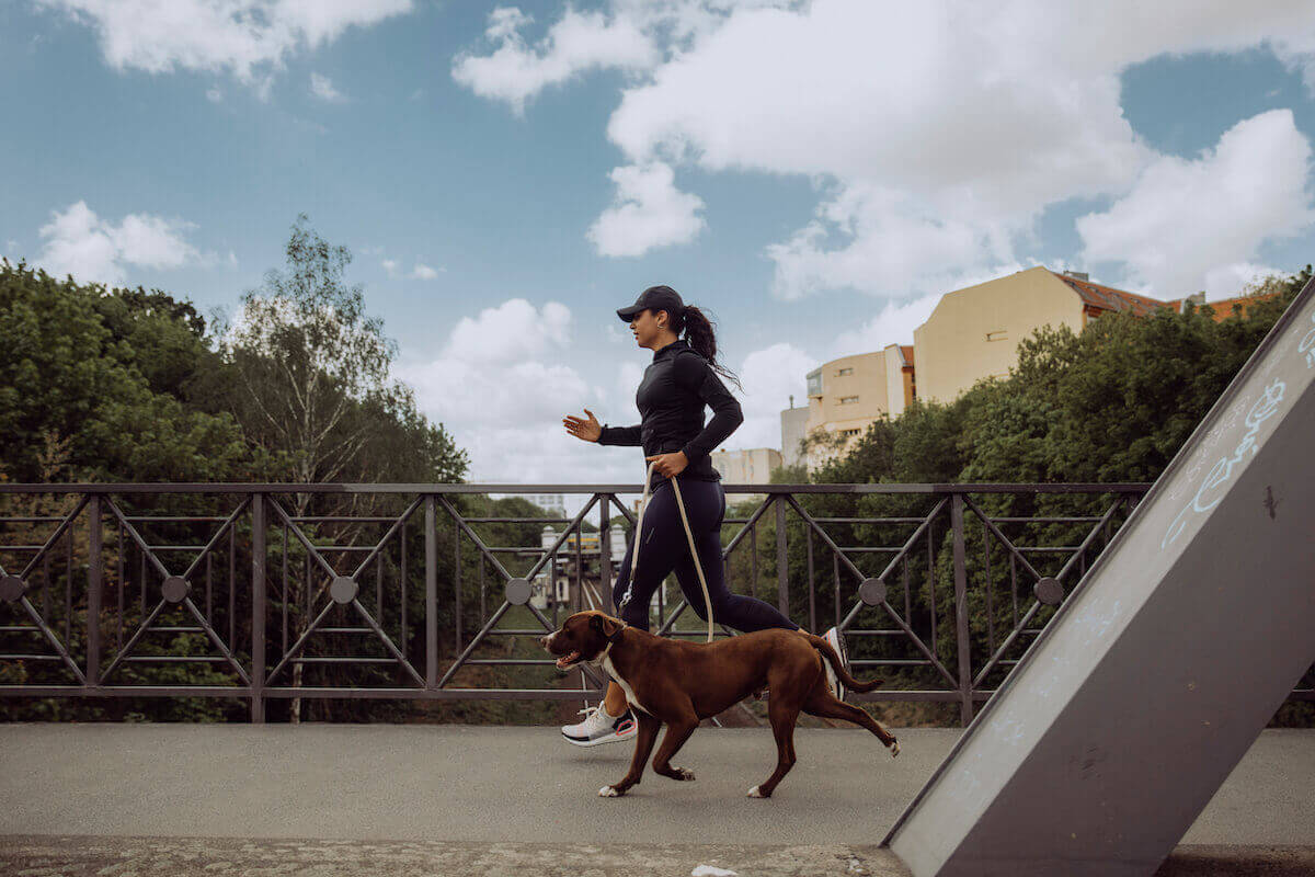A woman is running on a bridge with her dog