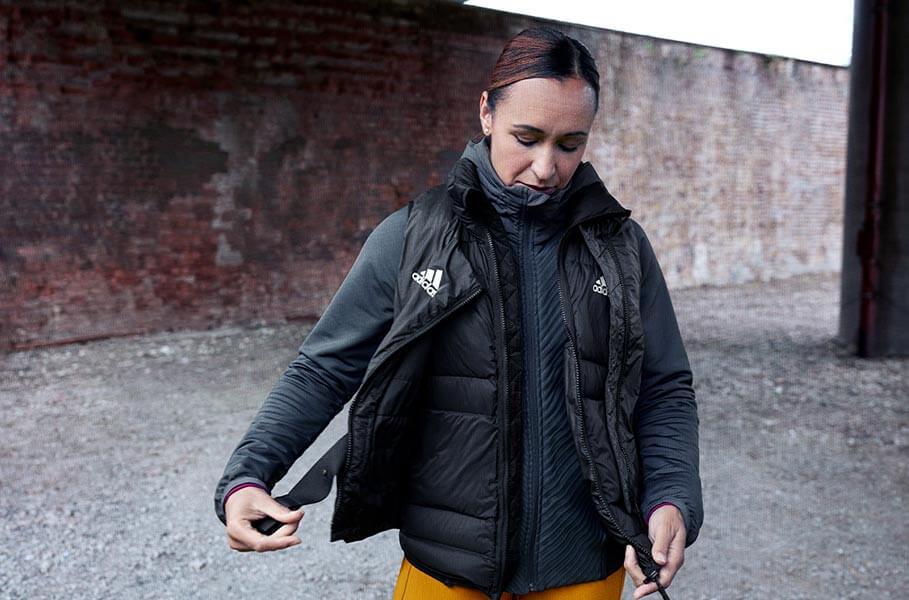 Eine Frau, in warmen adidas Sachen, bereitet sich auf das Laufen im Winter vor