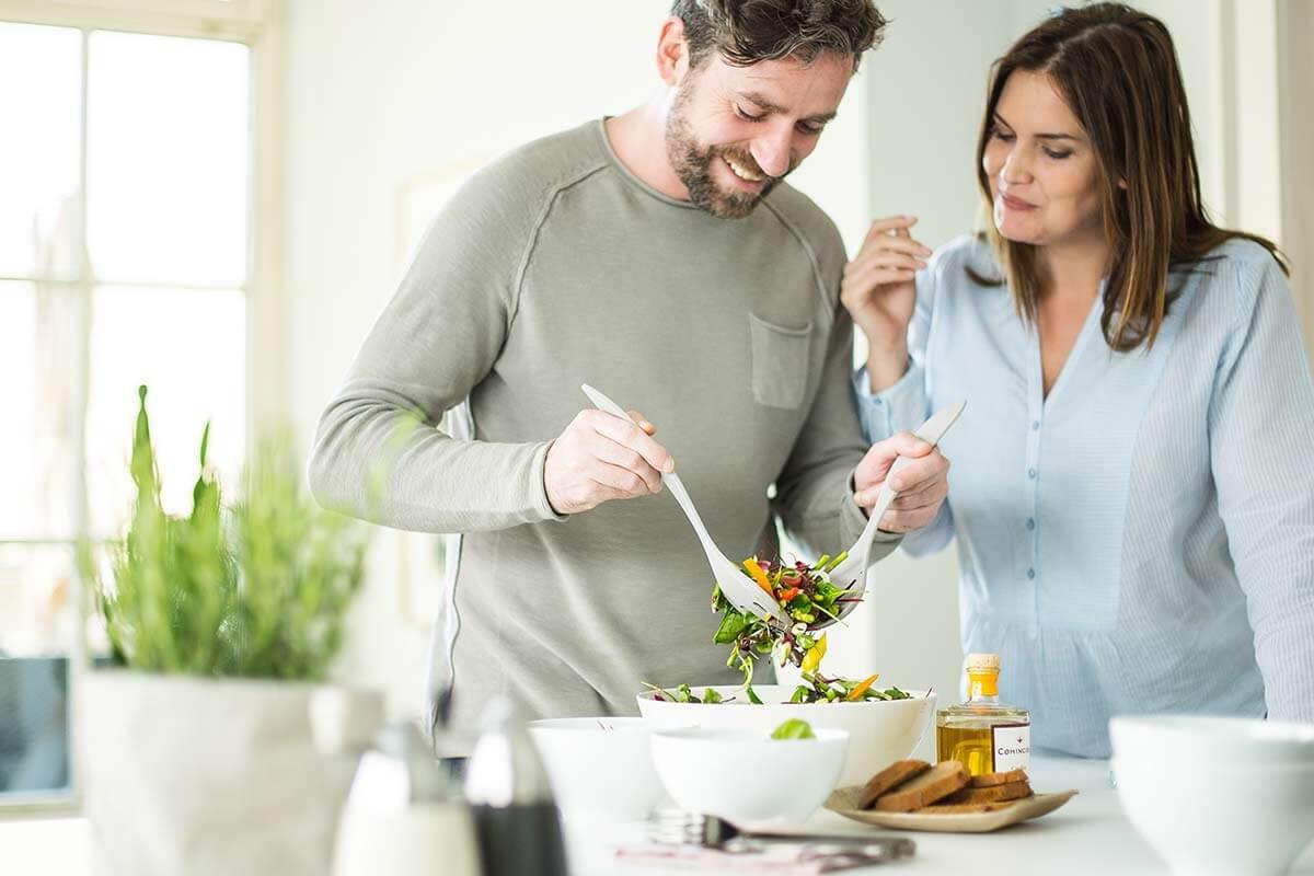 Coppia prepara insalata in cucina