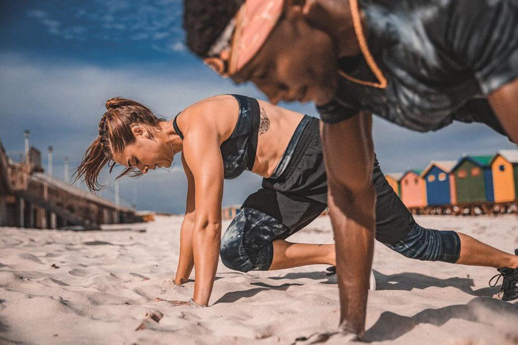 Couple is doing a workout at the beach to reduce stress
