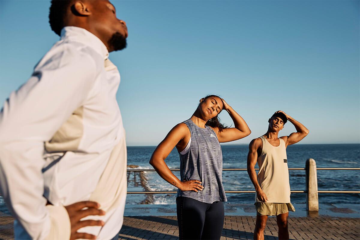 grupo de runners estirando al lado del mar