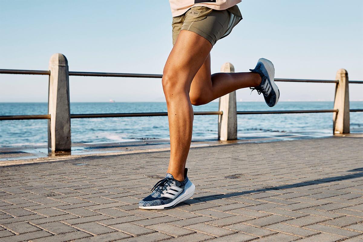 runner corre sull'asfalto in riva al mare