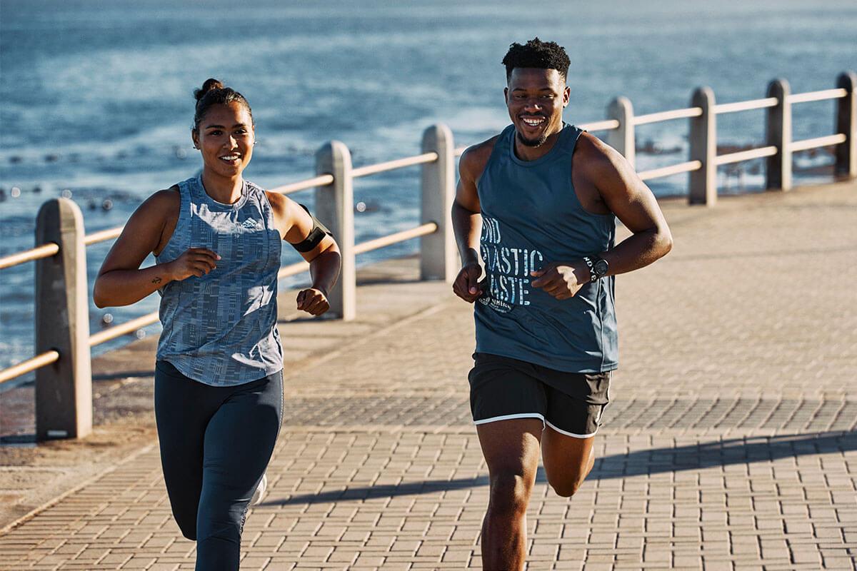 due persone corrono in riva al mare