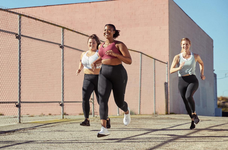 Três mulheres correndo pela rua e sorrindo