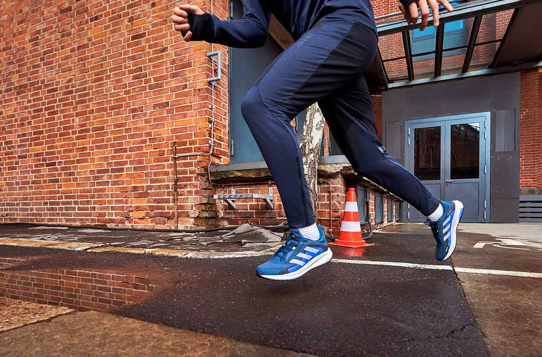 primo piano delle gambe di un runner con abbigliamento adidas