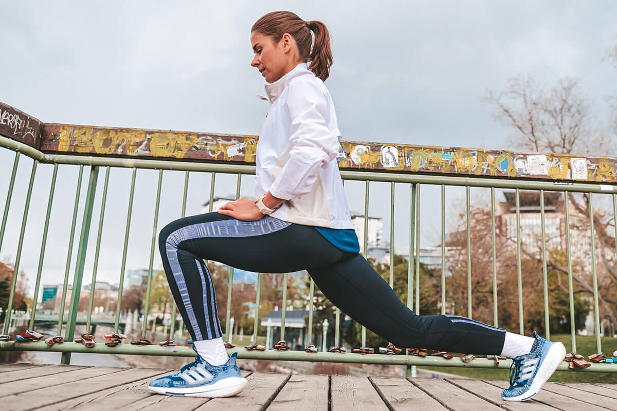 Mulher se alongando antes de correr para preparar a musculatura