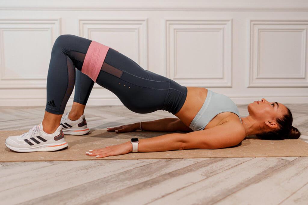 jambes-abdos-fessiers : une femme se muscle avec une bande de résistance