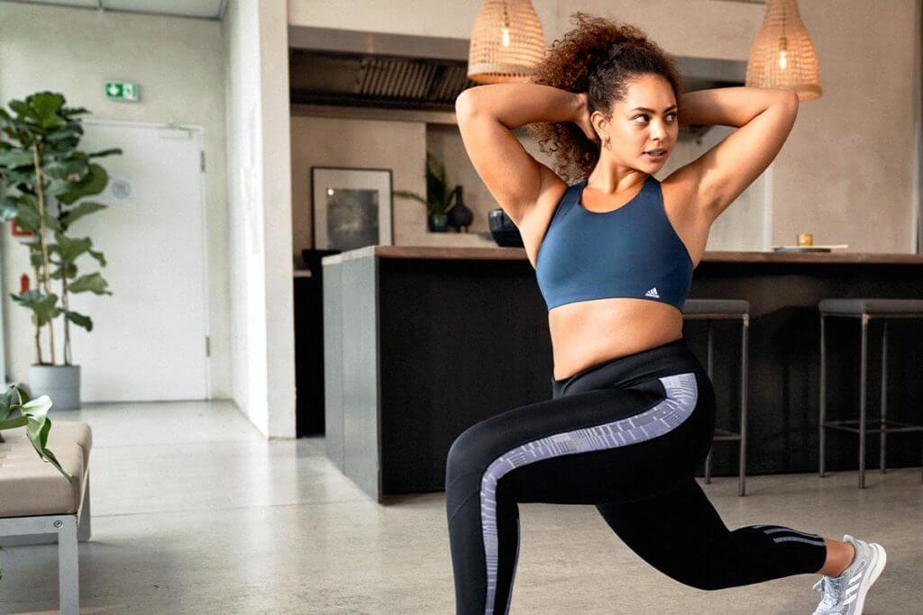 Una donna esegue un allenamento HIIT a casa