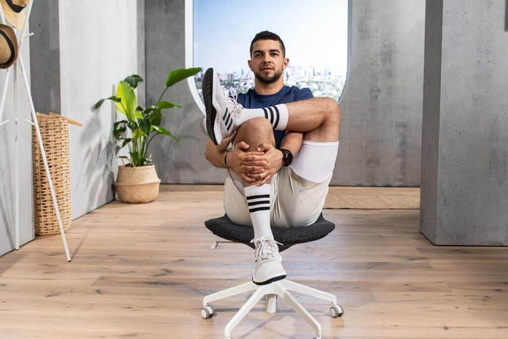 Un jeune homme pratique un exercice de yoga sur chaise