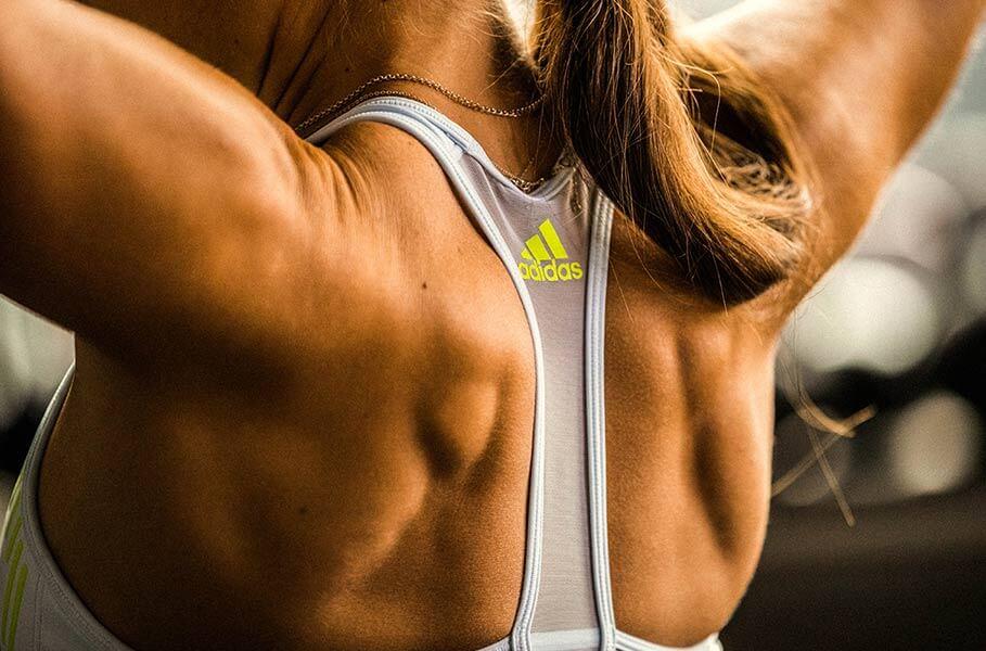 Costas de mulher com top da adidas durante treino de força