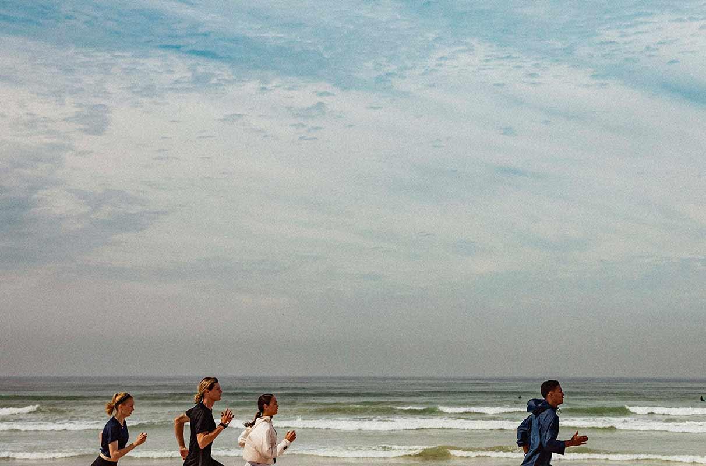 Grupo de pessoas correndo na praia para melhorar a técnica de corrida