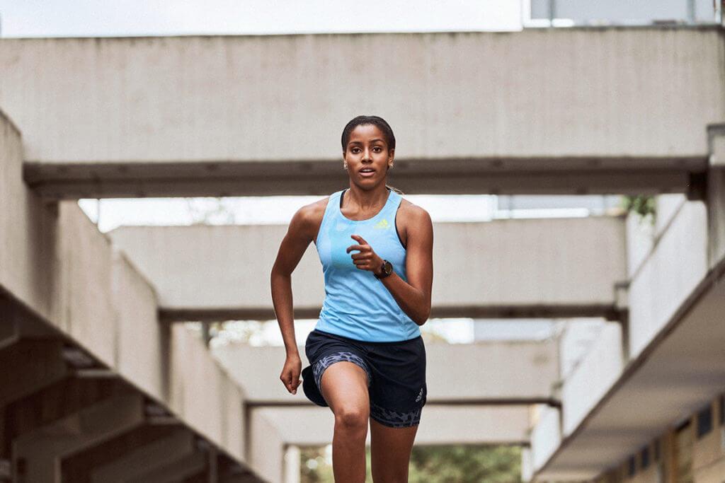 Mujer con ropa de running de adidas corriendo al aire libre