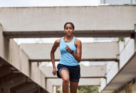 Mulher correndo focada para aprimorar a resistência mental
