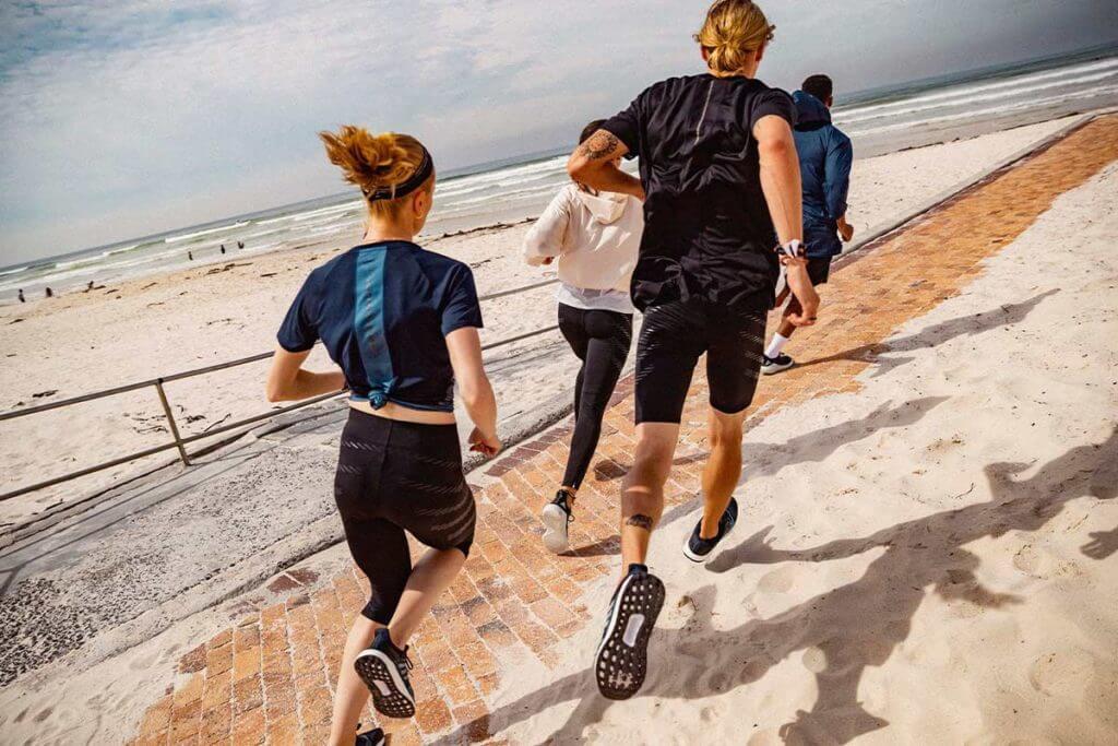 Grupo correndo na praia para melhorar a técnica de corrida