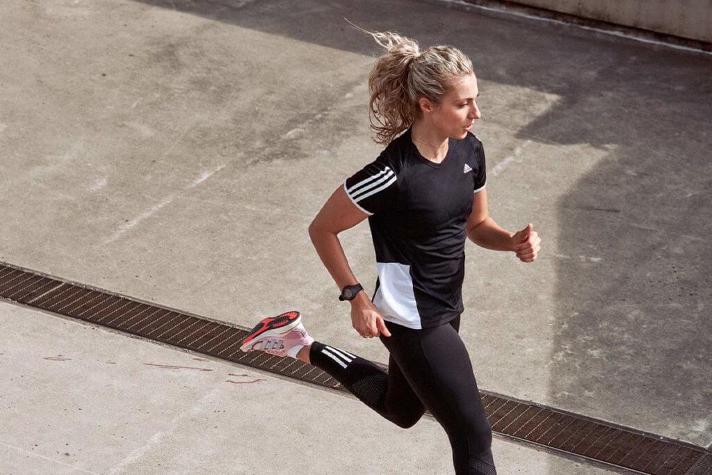 Mulher cansada ao correr na rua por sofrer com alergias respiratórias