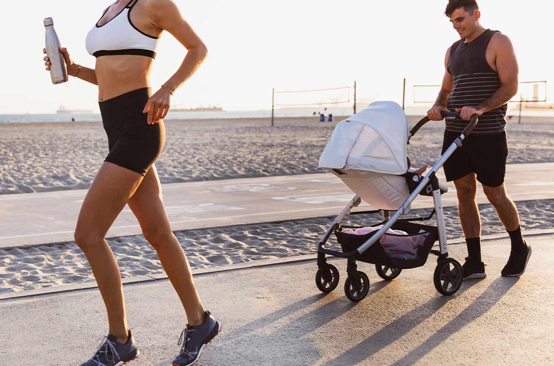 un uomo e una donna corrono col passeggino