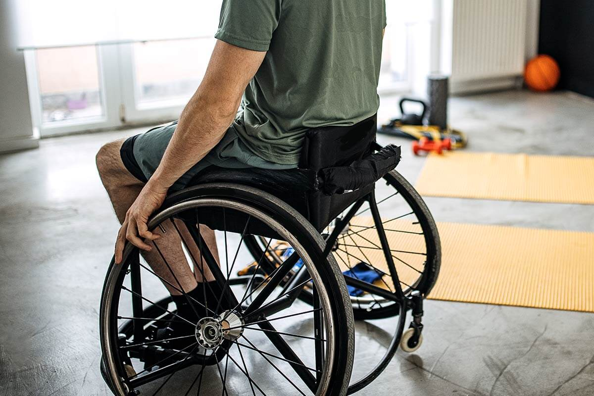 Cadeirante próximo a aparelhos de ginástica para treinar