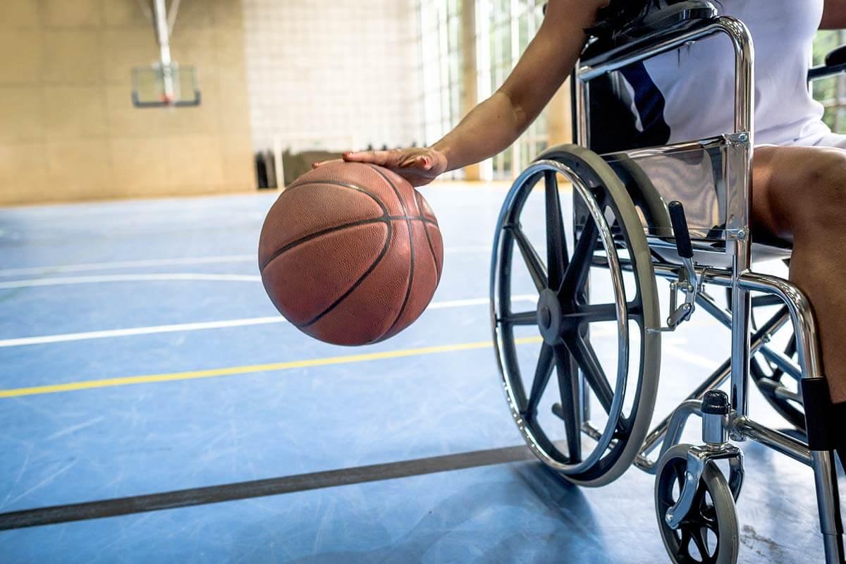 cadeirante quicando bola de basquete em uma quadra esportiva