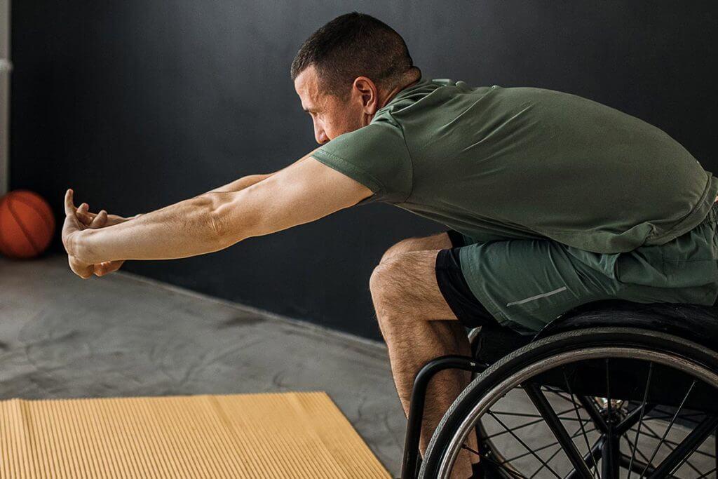 Homem se alongando na cadeira de rodas