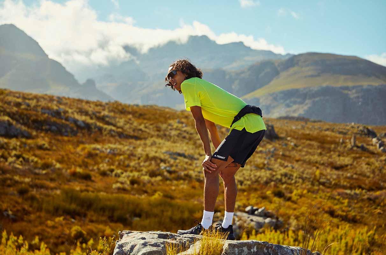 Pessoa descansando durante uma corrida em trilha sobre as montanhas