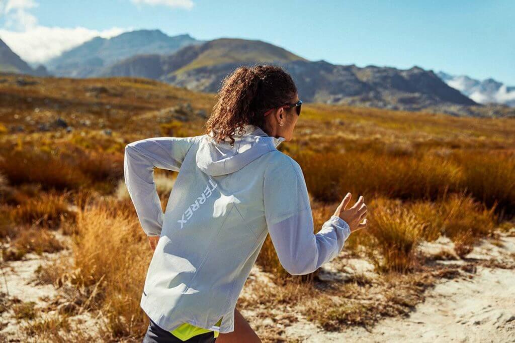 Pessoa de casaco branco correndo em uma trilha