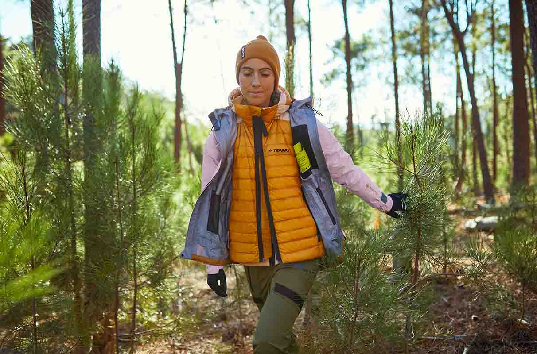 mujer haciendo senderismo por el bosque con un chaleco adidas terrex